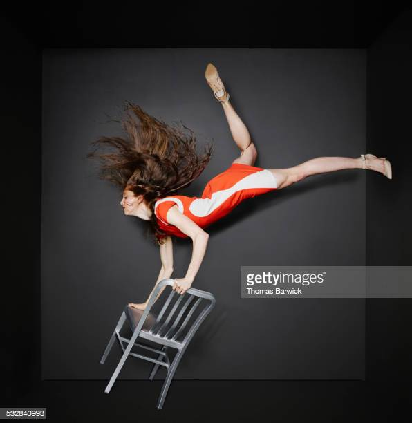 Woman doing handstand on chair balanced on one leg