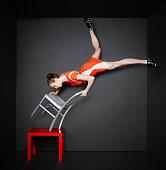 Woman doing handstand on chair balanced on table