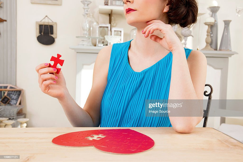 Woman doing heart shaped jigsaw puzzle holding piece : Stock Photo