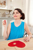 Woman doing heart shaped jigsaw puzzle holding piece