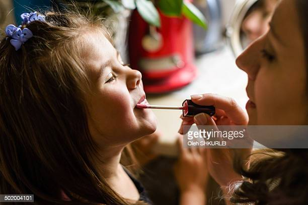 Woman doing makeup to a little girl
