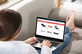 Woman Sitting On Couch Doing Online Shopping On Laptop