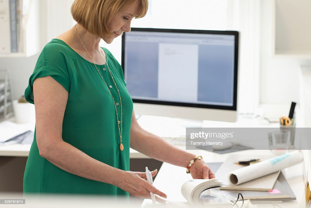 Woman doing paperwork in office : Stock Photo