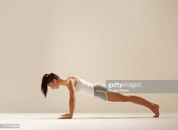 Woman doing press up on white set.