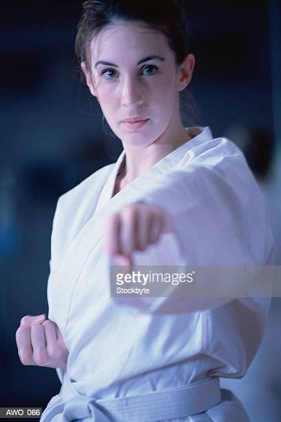 Woman doing punching exercise, wearing martial arts outfit