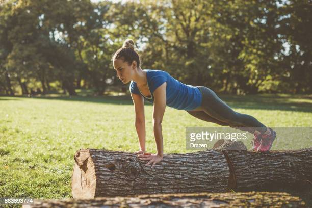 Woman doing push ups on logs