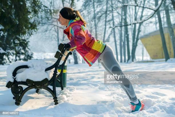 Frau tut Push Ups im Freien in einer Parkbank