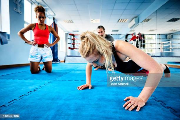 Woman doing push ups with fitness trainer in the gym