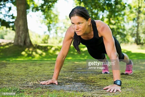 Woman doing push-ups in garden