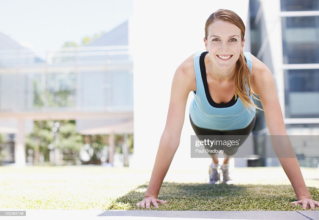 Woman doing push-ups in urban setting