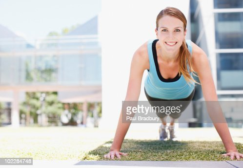 Woman doing push-ups in urban setting : Stock Photo