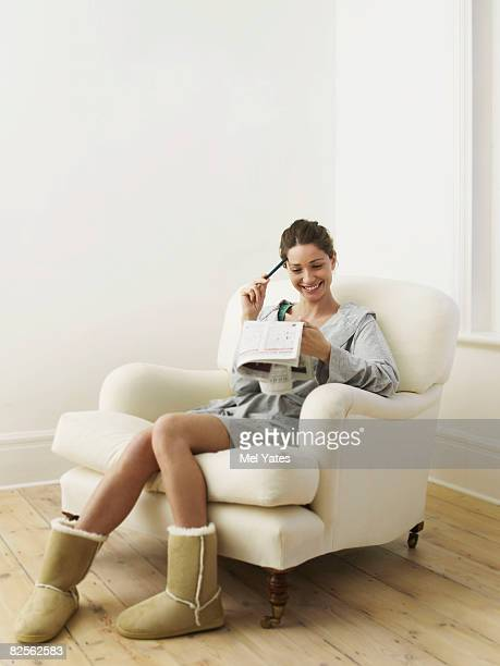 Woman doing puzzle in newspaper