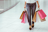 Beautiful young woman in white blouse and jeans holding shopping bags and doing shopping in mall, cropped