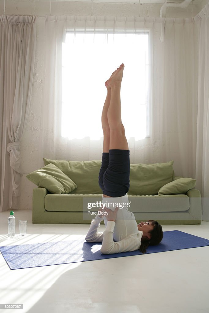 Woman doing shoulder stand on blue mat