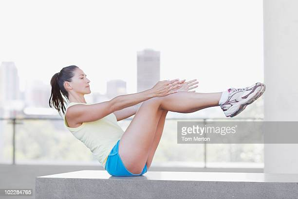Woman doing sit-ups in urban setting