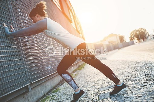 Woman doing sport warming exercise on the street