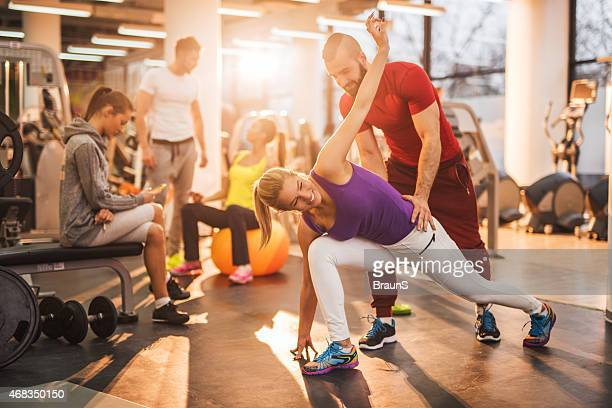 Woman doing stretching exercises with the help of personal trainer.