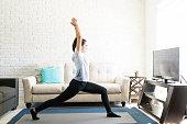 Full length hispanic woman doing yoga on exercise mat at home