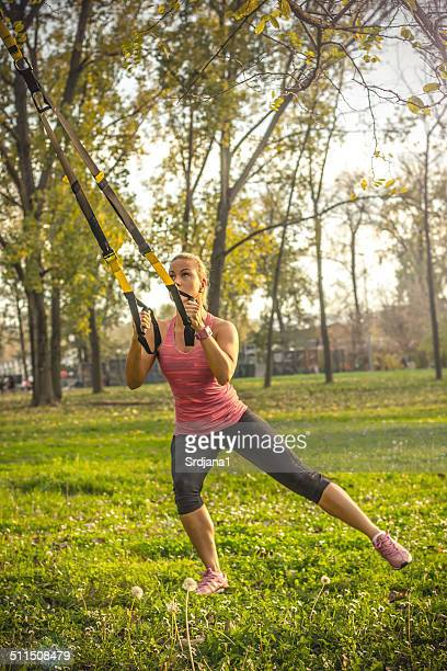 Woman doing suspension training in the park