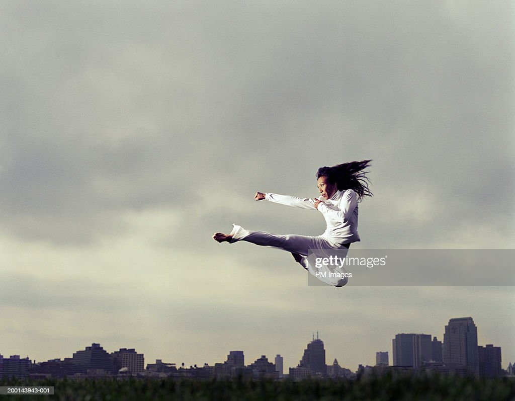 Woman doing tae kwon do kick in park, low angle view : Stock Photo