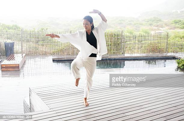 Woman doing tai chi outdoors