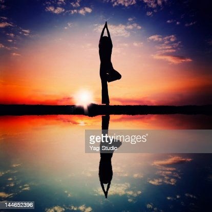 Woman doing tree pose silhouette : Stock Photo