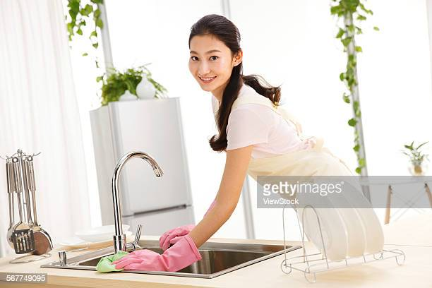 Woman doing washing-up in kitchen
