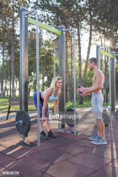 Woman doing weightlifting exercises being assisted by her trainer