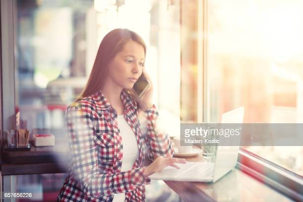 Woman doing work in cafe, using laptop and mobile phone