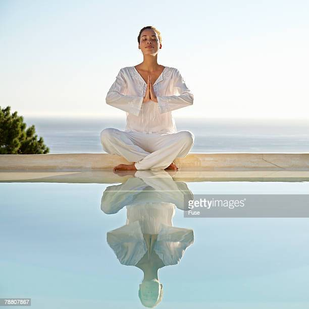 Woman Doing Yoga by Swimming Pool