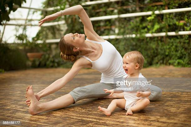Woman doing yoga exercise while baby having fun