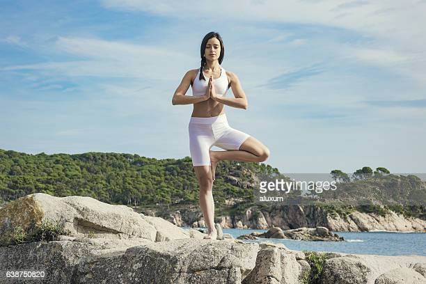 Woman doing yoga exercises at the sea
