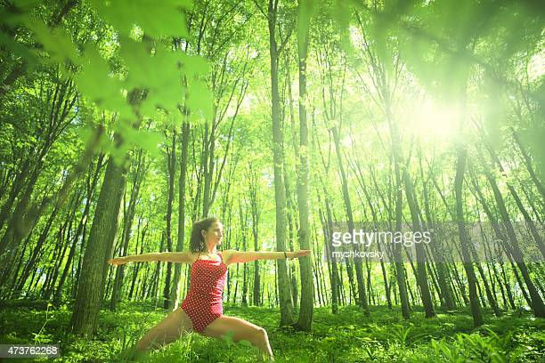 Woman doing yoga in beech forest