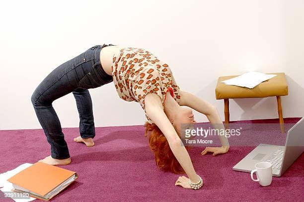 woman doing yoga looking at computer