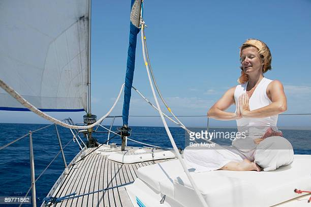 Woman doing yoga on Sailing Boat