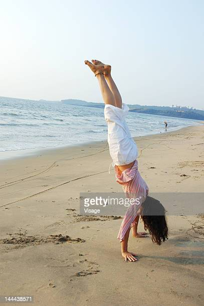 Woman doing Yoga on the beach side