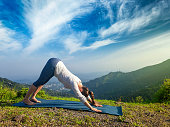 Young sporty fit woman doing yoga asana Adho mukha svanasana - downward facing dog - in Surya Namaskar Sun Salutation outdoors in Himalayas in the morning