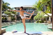 Woman doing yoga poolside at luxury resort