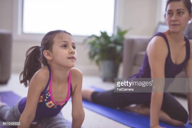 Femme faisant yoga pose à l'intérieur avec une fille