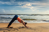 Yoga outdoors - young sporty fit woman doing Ashtanga Vinyasa yoga asana Adho mukha svanasana - downward facing dog - at tropical beach. Kerala, India