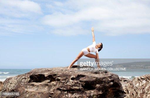 Woman doing yoga triangle pose on beach