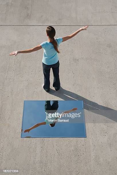 Woman doing yoga with arms up and mirror on ground with reflection