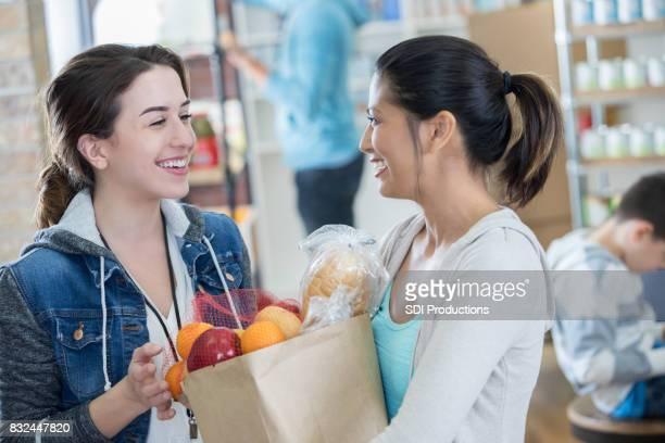 Femme donne sac de nourriture pour les sans abri