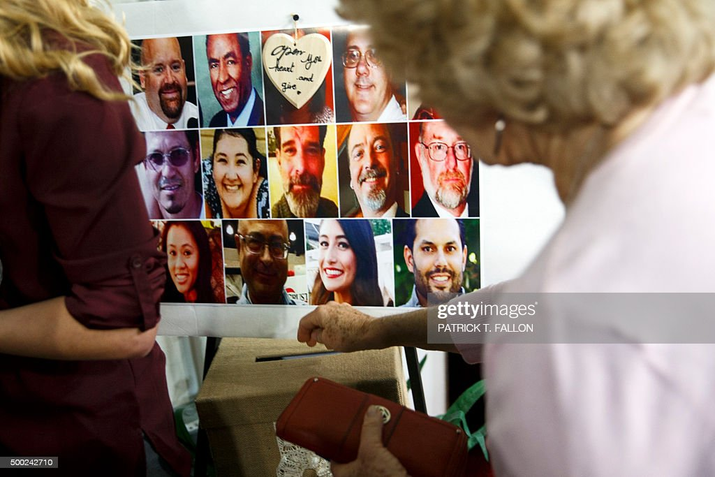 A woman donates money as a poster showing all 14 victims is displayed during an interfaith memorial service at the Islamic Center of Redlands for the...
