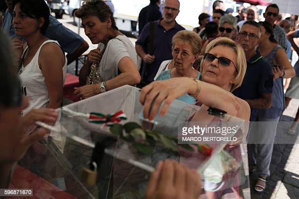 A woman donates money during a charity event in Piazza San Carlo in Turin on August 28 whose profits are to help the population hit by the quake in...
