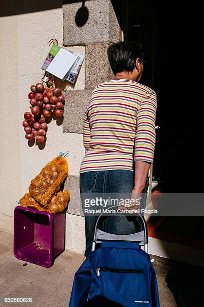 Woman dragging shopping trolley bag coming in traditional food shop and onions on display at shop doorway