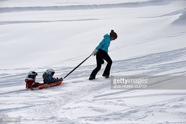 A woman drags a sled for her children at the ski resort of Courchevel on the French Alps which opened its ski slopes for a day on November 11 2016...