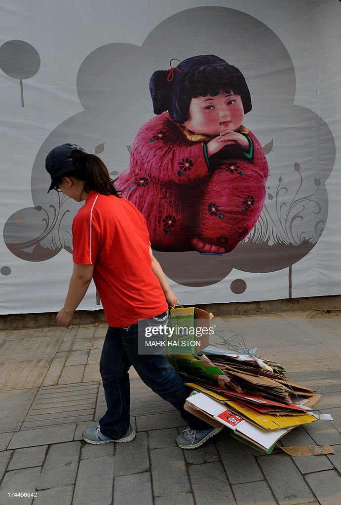 A woman drags cardboard past a 'Chinese Dream' promotion billboard beside the CCTV office tower in the Central Business District in Beijing on July 26, 2013. Decades of breakneck expansion have given China gleaming skyscrapers and sleek railways, but brought piles of debt and dubious financial instruments analysts say are a potential time bomb that could strike a blow against global growth. AFP PHOTO/Mark RALSTON