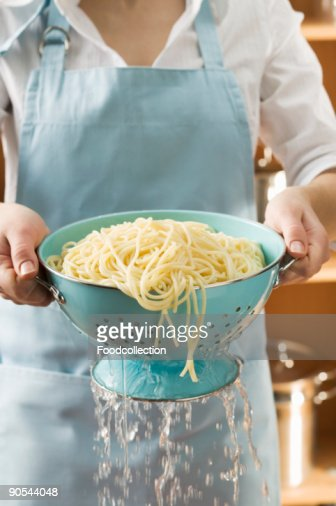 Woman draining cooked spaghetti, close up, mid section
