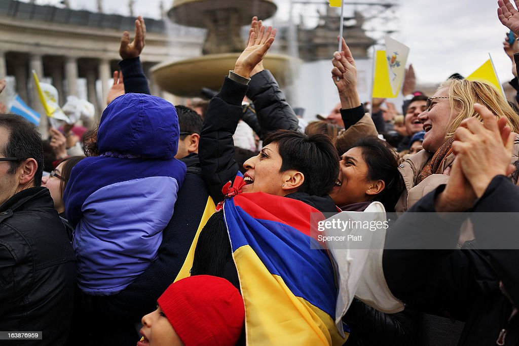 A woman drapes herself in the flag colors of Venezuela as crowds watch as Pope Francis appears in the window of his private residence in St Peter's Square to give his first Angelus blessing on March 17, 2013 in Vatican City, Vatican. The Vatican is preparing for the inauguration of Pope Francis on March 19, 2013 in St Peter's Square.